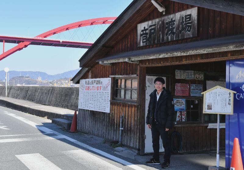 渡船乗り場に立つ数田さん。奥の看板には寄付した人の名前が並ぶ