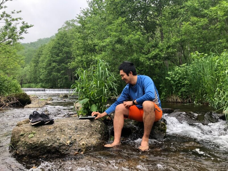 渓流の岩をデスクにリモートワーク