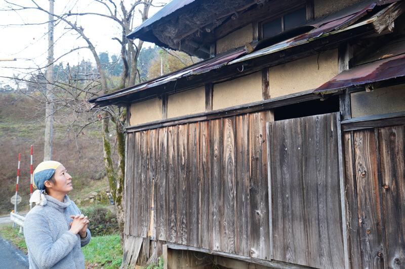 藁葺きの屋根にトタンをかぶせた古い家屋の前で説明する小山さん