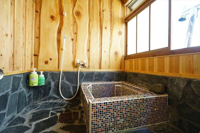 ▶室内の五右衛門風呂はシャワーもあり。壁面の木は地元の木材を使用。
