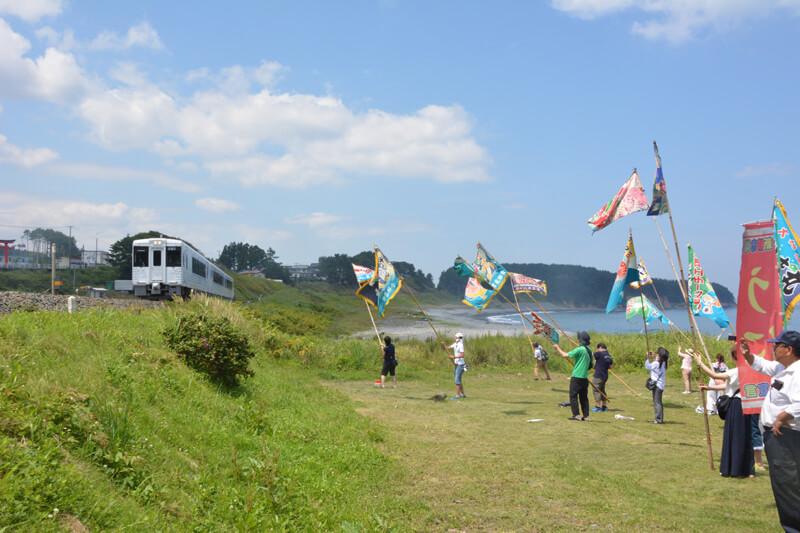 列車に向かって大漁旗を振る様子