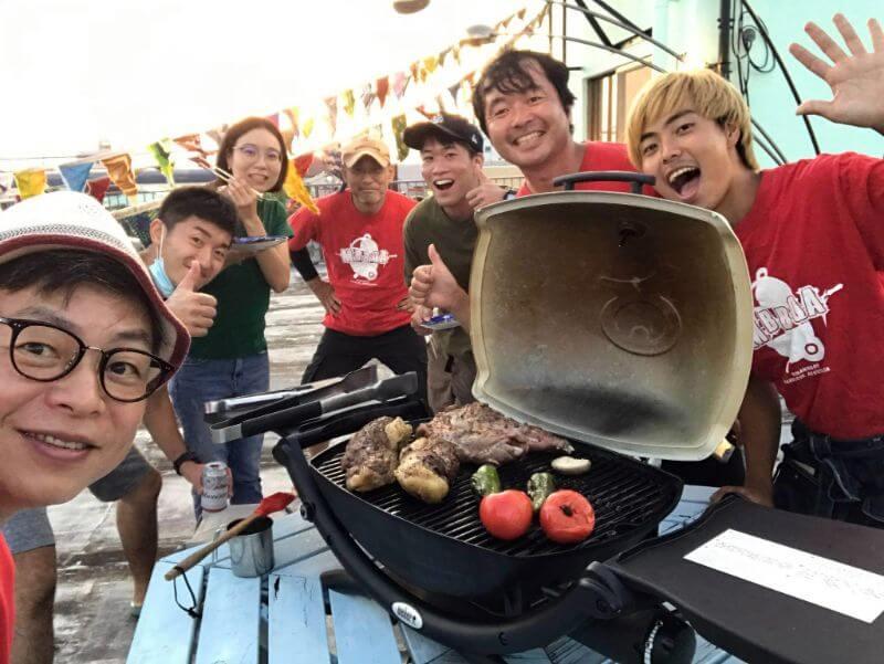 地元の人たちと、イノシシの肉を使ったバーベキューを楽しむ萬隊メンバー