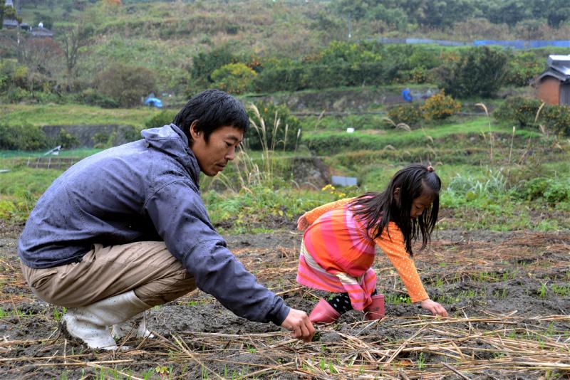 種をまく三浦さんと子ども